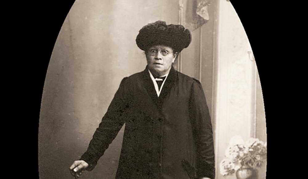 Karoline Graves omkring 1920, klar til at tage ud som avisskribent for at finde stof til sine artikler. Den lokale, landskendte folkemindesamler opsøgte i 1925 Ubbys nye forsamlingshus for at blive inspireret af rejsebeskrivelser fra USA. Foto: Dansk Folkemindesamling.