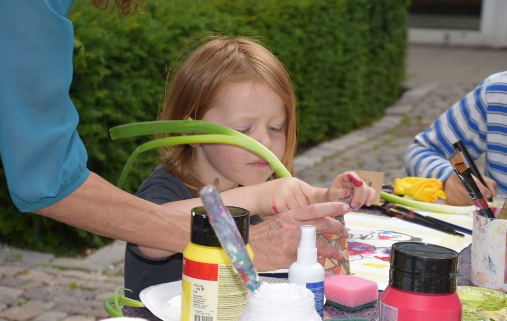 To gange om ugen i skolernes sommerferie tegner og maler den lokalebilledkunstner Ditte Forchhammer med børnene i gården ved Kalundborg Bibliotek. Foto: Gitte Korsgaard.