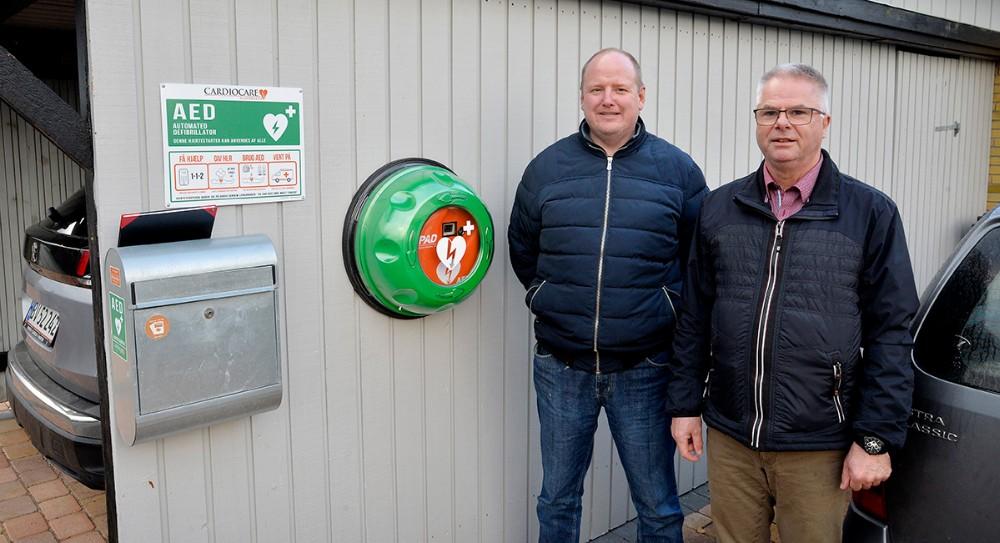 Den ene af de to nye hjertestartere er sat op hos TommyJensen, til venstre, her sammen med formand forAarby- lyngs grundejerforening,Palle lykke Jensen. Foto: Jens Nielsen