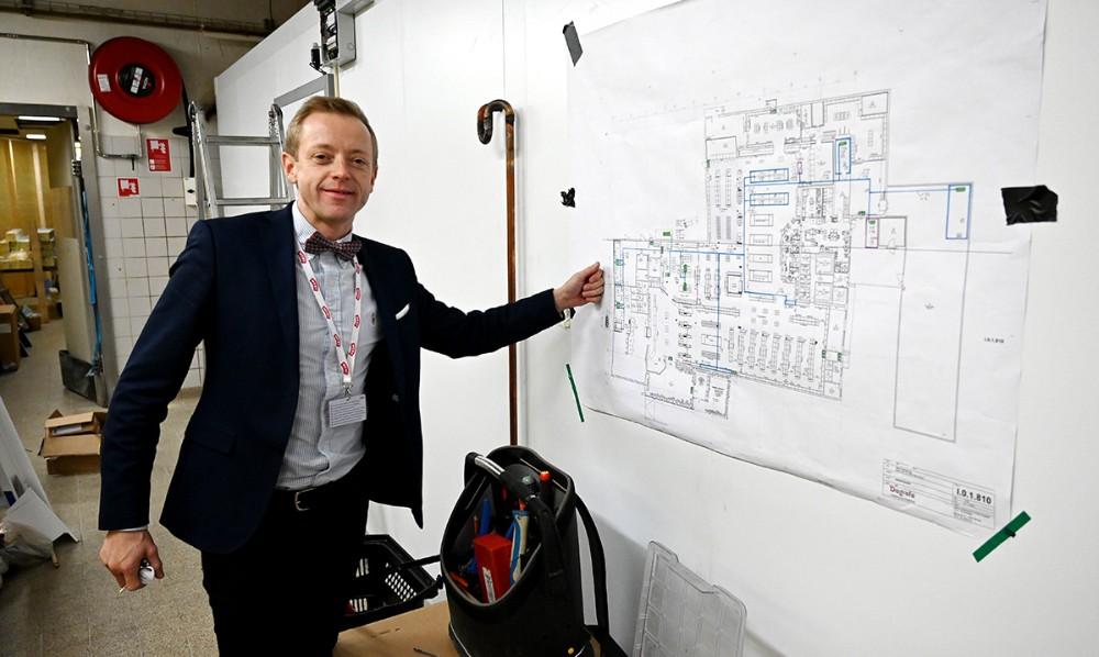 Meny købmand Peter Egebæk ved den tegningenover de mange nye rørføringer i forretningen. Foto: Jens Nielsen
