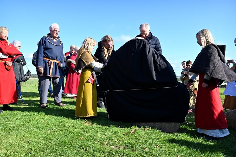 De to vikingepiger Sigrid og Vigga trak det sorte klæde væk som dækkede den nye runesten, da Bertel Haarder snittede snoren. Foto: Jens Nielsen