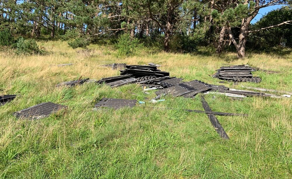 Gamle tagplader, nedløbsrør og brædder er smidt i naturen. Privatfoto