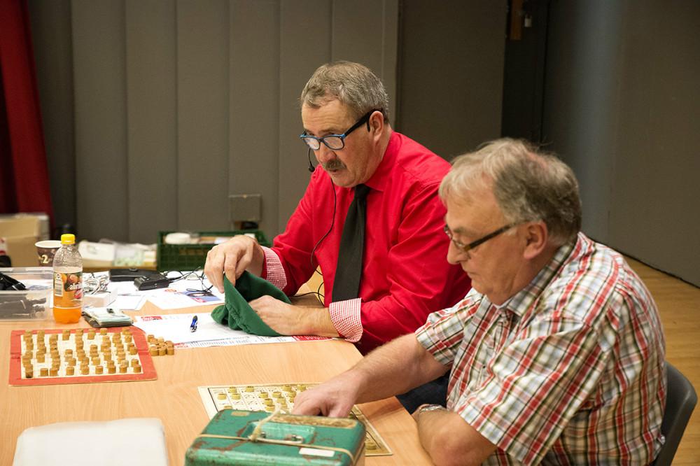Niels-Erik Sørensen (i rød skjorte) i gang med at råbe numre op i en lind strøm til årets julebanko. Foto: Jens Nielsen
