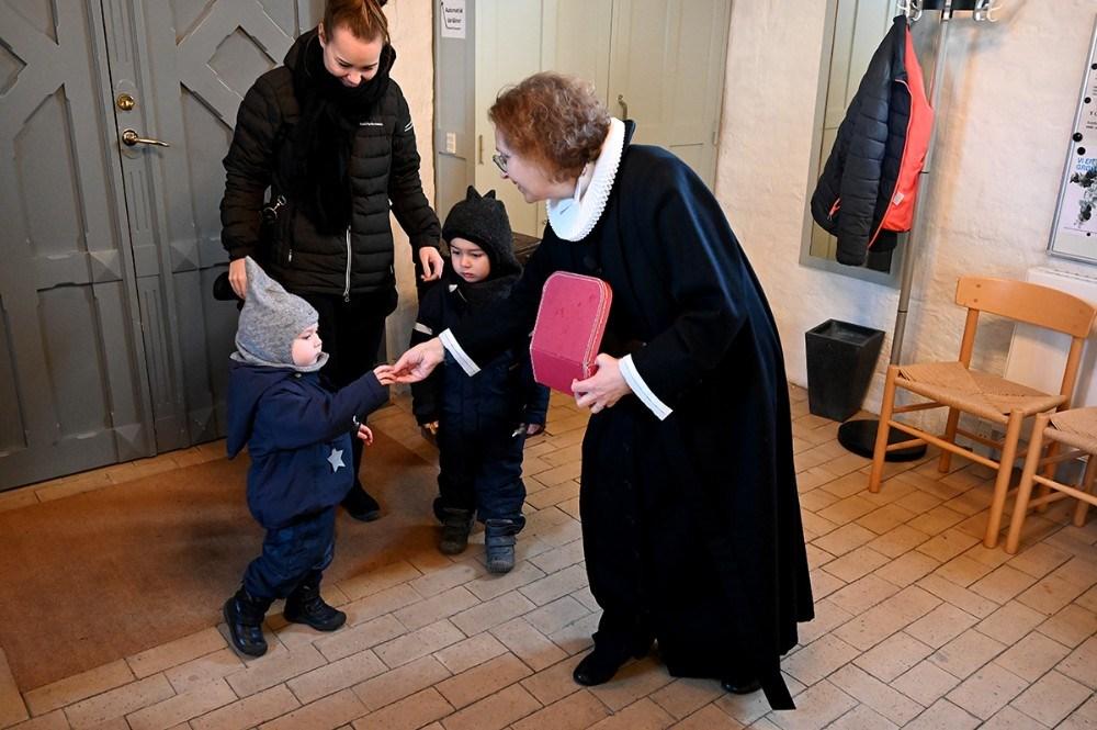 Sognepræst Lisbeth Dyxenburg forsynede hvert barn med to guldmønter, som de så skulle betale med for at komme ind i kirken. Foto: Jens Nielsen