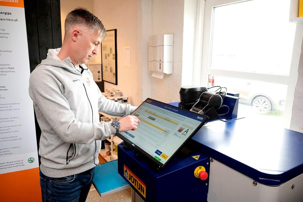 Jack Egebjerg, butikschef i ProPainting, i gang med den nye blandemaskine som kan tone malingen i lige den farve kunden ønsker. Foto: Jens Nielsen