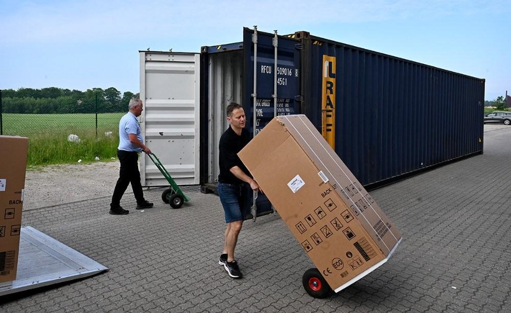 Jesper Abkjær Petersen og Steen Jensen i gang med at tømme containeren sammen med firmaets medarbejdere. Foto: Jens Nielsen