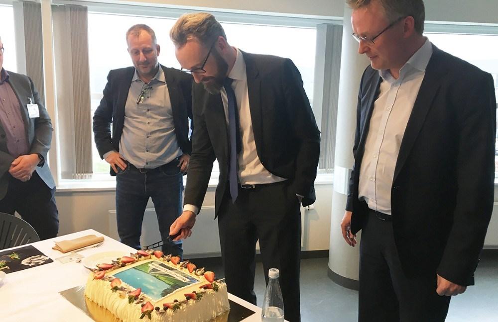 Transportminister Ole Birk Olesen skar kagen for, mens Jacob Jensen, til højre i billedet, så til. Privatfoto