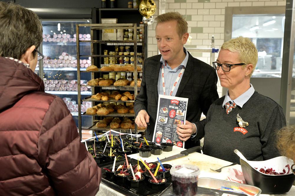 Købmand Peter Egebæk præsenterer nytårsmenuen for en kunde, her sammen med Pia Dyngby. Foto: Jens Nielsen