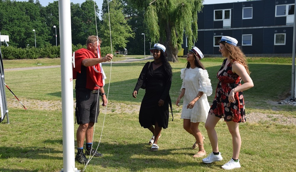Laura Dyring Jeppesen, Anood Yusuf  og Hibeh A. Al-Rekabi  blev årets første studenter fra Kalundborg Gymnasium. Her hejser de flaget. Foto: Gitte Korsgaard.