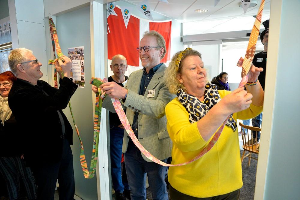 Kelly, frivillig i Symb, Keld Christensen, medstifter af Symb og Helle Freiesleben fra Solsikken, bandt et bånd sammen som blev hængt op over indgangen til de nye lokaler. Foto: Jens Nielsen