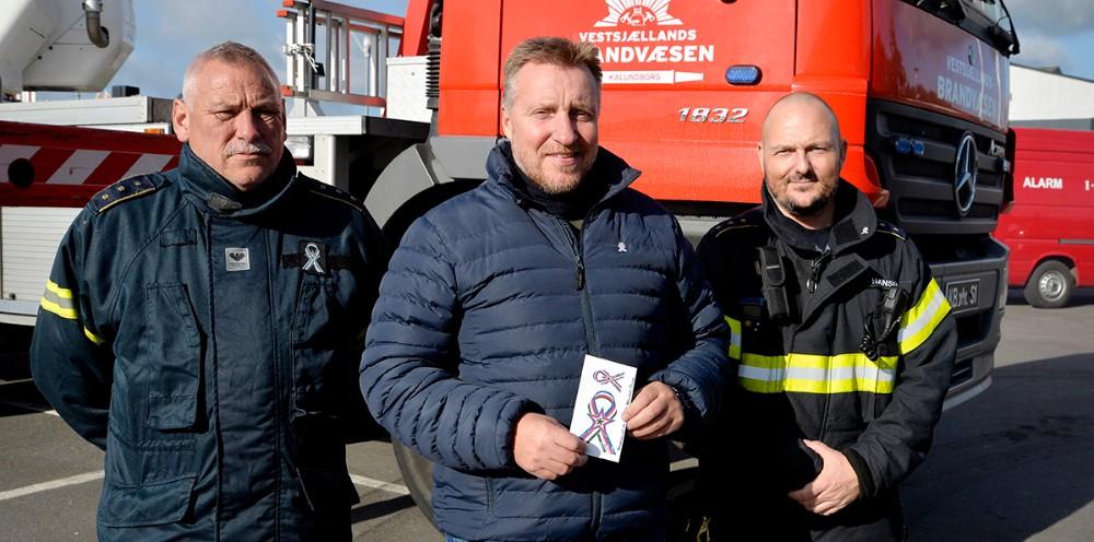 Michael Jensen i midten, sammen med de to brandmænd og medlemmer af donationsudvalget,Per Hasselbalch og Ulrik Kristian Hansen. Foto: Jens Nielsen