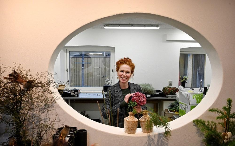 Fra forretningen er der kik til blomsterværkstedet, her er det Lena Rasmussen der er i gang med at binde en buket. Foto: Jens Nielsen