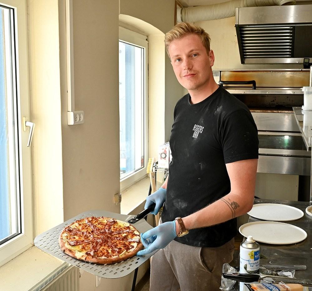 Asger Øgelund med en pizza som lige er kommet ud af ovnen. Foto: Jens Nielsen