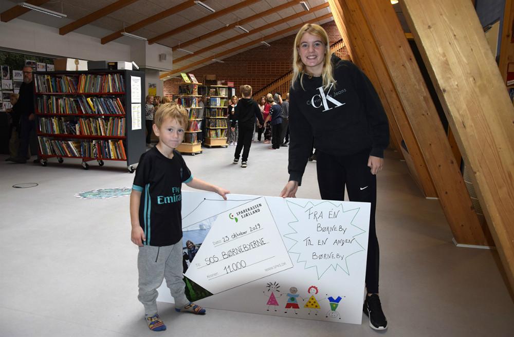 Anton fra 0. klasse og Caroline fra 7. klasse overrækker gavechecken til SOS Børnebyerne onsdag formiddag på Svebølle Skole. Foto: Gitte Korsgard.