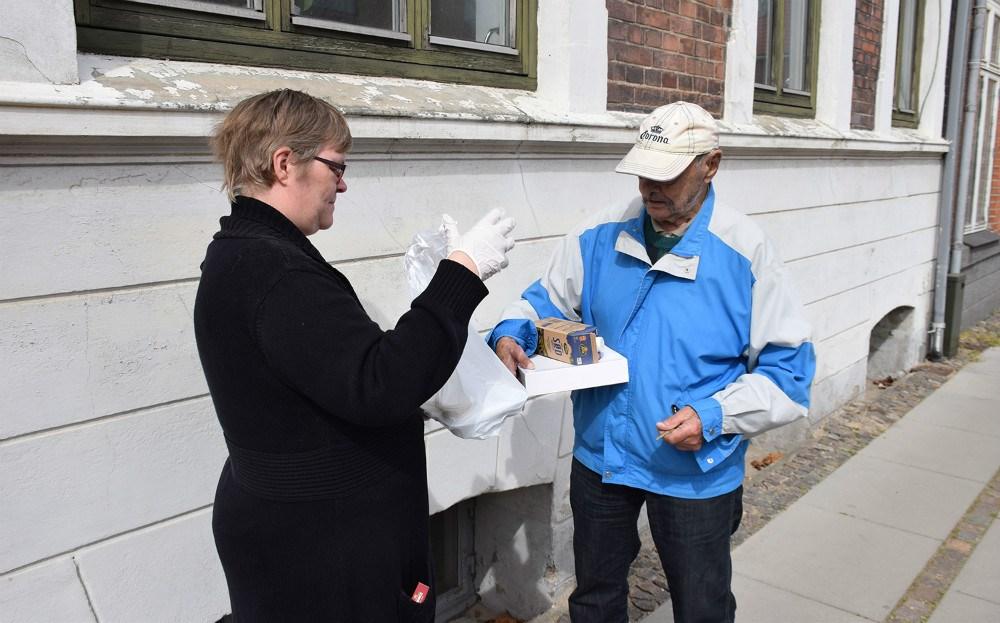 Anton Søgaard kommer normalt i medborgerhuset i Kalundborg, men da det pt. erlukket grundet COVID-19 situationen, får han nu mad bragt til døren fra Medborgerhuset. Her er det Anne Nielsen, der er frivllig i Medborgerhuset, der afleverer maden.Foto: Gitte Korsgaard.