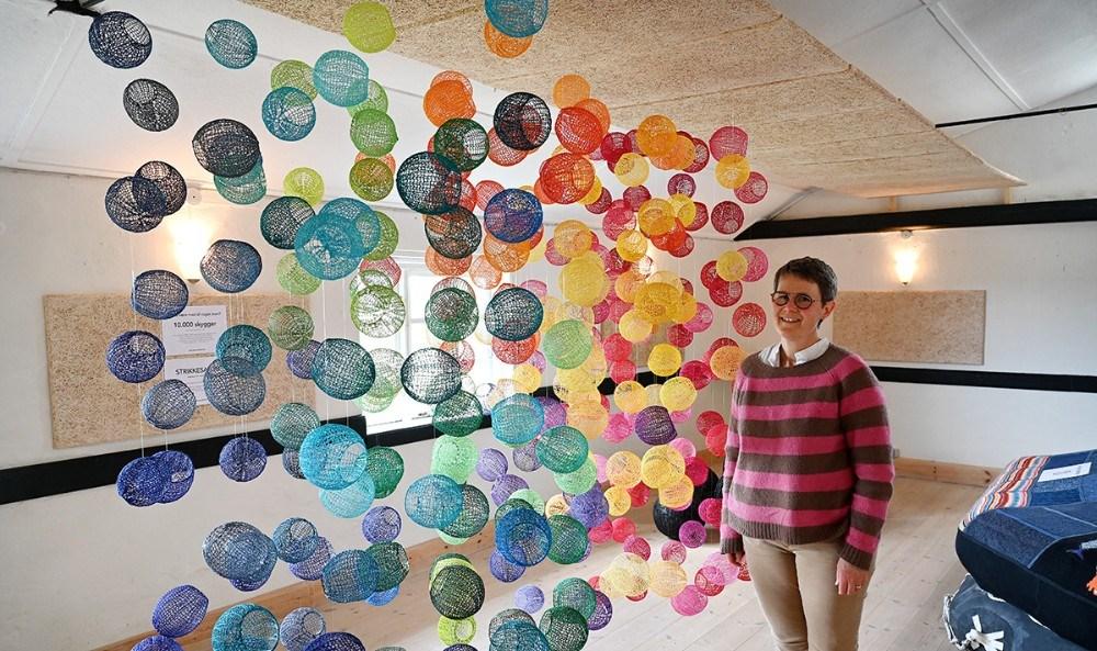 Tekstilkunstner Sisse Fog Odgaardhar hele pinsen udstillet en lille del af sit store projekt med at strikke 10.000 skyggekugler på Mødestedet Hallebyore. Foto: Jens Nielsen