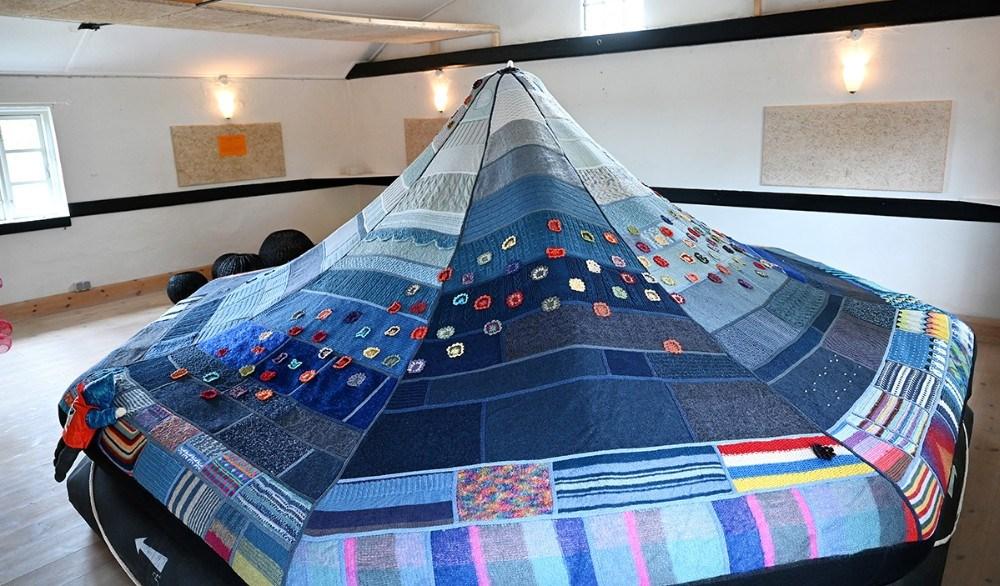 """En rednings flåde fra det tidligere crowd-knitting projekt Kuldsejlinger. Her blev over 2000 kuldsejlede strikkeprojekter forvandledet til en storslået tekstil installation, for at sætte fokus på hvad der sker når vi tør tale højt om vores """"mislykninger"""". Foto: Jens Nielsen"""