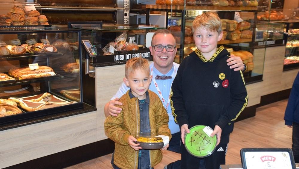 Nikolaj Andersen, der er kolonialchef hos Meny Kalundborg, gav kage til de to vindere af konkurrencen, Felix på 4 år (tv) og Victor på 8 år. Foto: Gitte Korsgaard.
