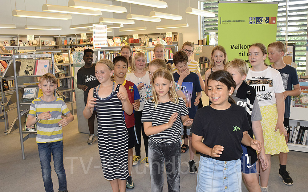 Signe Staunshøj Larsen har netop fået overrakten pris for sin historie. Det fejrer hun på Ubby Bibliotek sammen med sin klasse - 4. klasse fra Ubby Fri- og Efterskole. Her danser klassen for Stine, da hun blev inspireret til sin historie af en sang. Foto: Gitte Korsgaard.