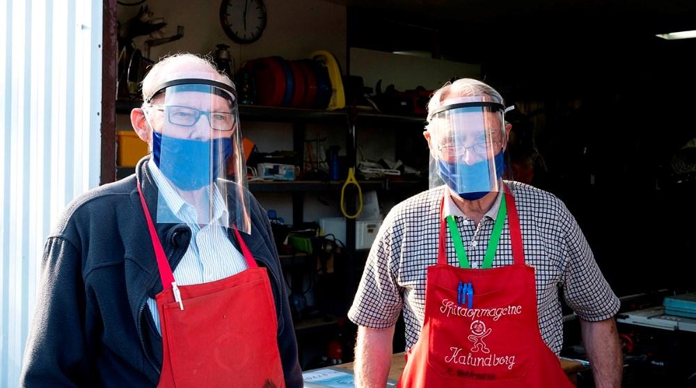 Et par af de mange frivillige iført mundbind og visir, klar til at tage imod kunder. Foto: Jens Nielsen