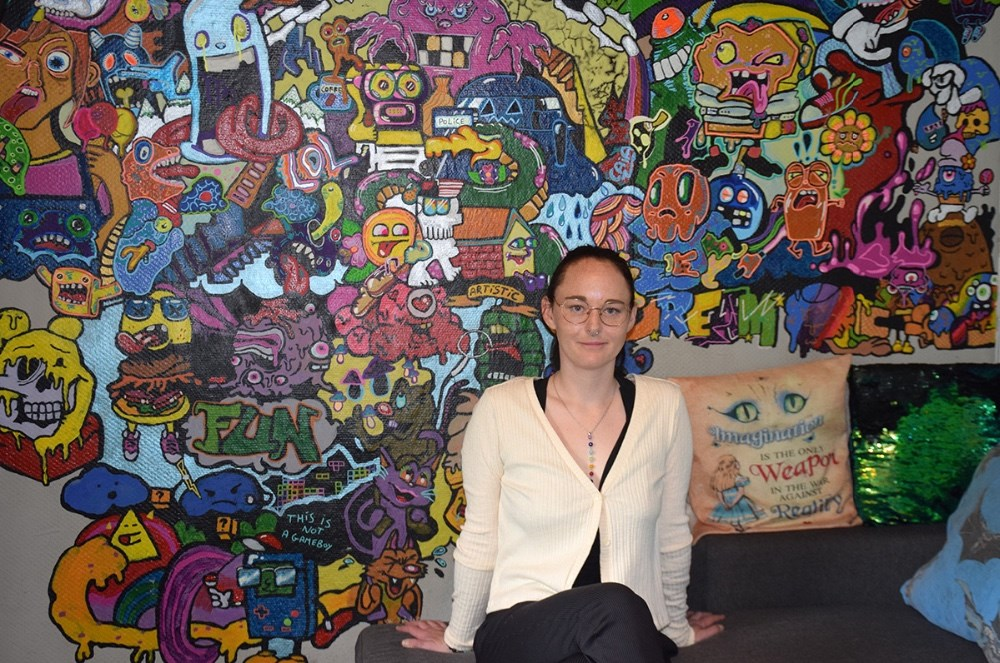 Caia Riemer foran vægmaleriet i sin stue, som hun begyndte at lave, da COVID-19 lukkede Danmark ned. Foto: Gitte Korsgaard.