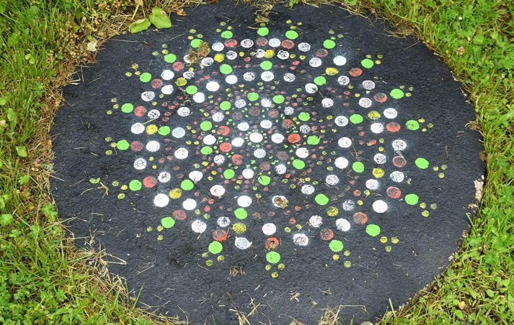Selv brønddækslet er malet i fine farver i Caia Riemers have. Foto: Gitte Korsgaard.