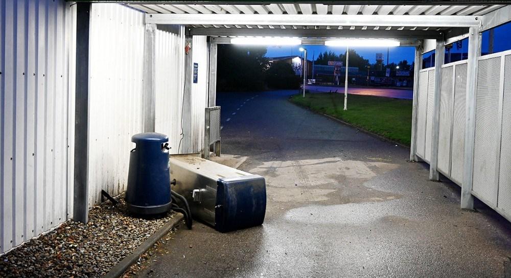 Vanvidsbilisten nedlagde et skilt, kørte hen over en græsplane, mellem to lygtepæle, ind gennem tankens pusleplads hvor en støvsuger blev påkørt inden bilen standsede midt på pladsen. Foto: Jens Nielsen