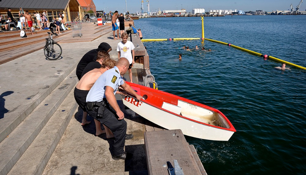 Et par store drenge hjalp politiet med at få optimistjollen på land og tilbage hvor den hører til på legepladsen i havneparken. Foto: Jens Nielsen