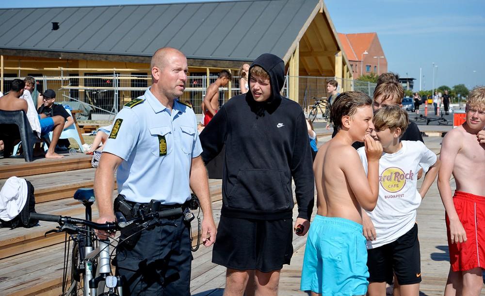 Jesper Engel fra lokalpolitiet i Kalundborg i snak med et par af de mange unge som opholder sig i havneparken. Foto: Jens Nielsen